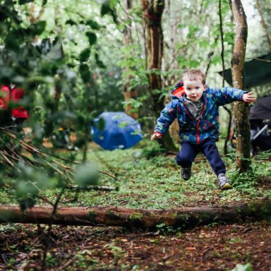 Forest School   boy jumping over log
