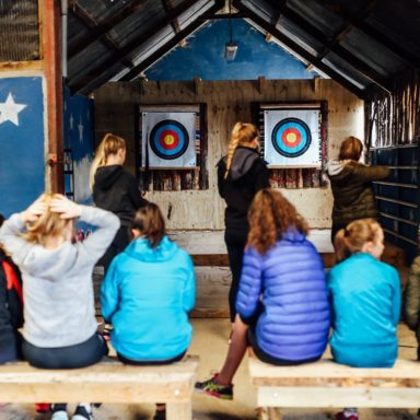 Archery   group on benches watching 2 girls fire