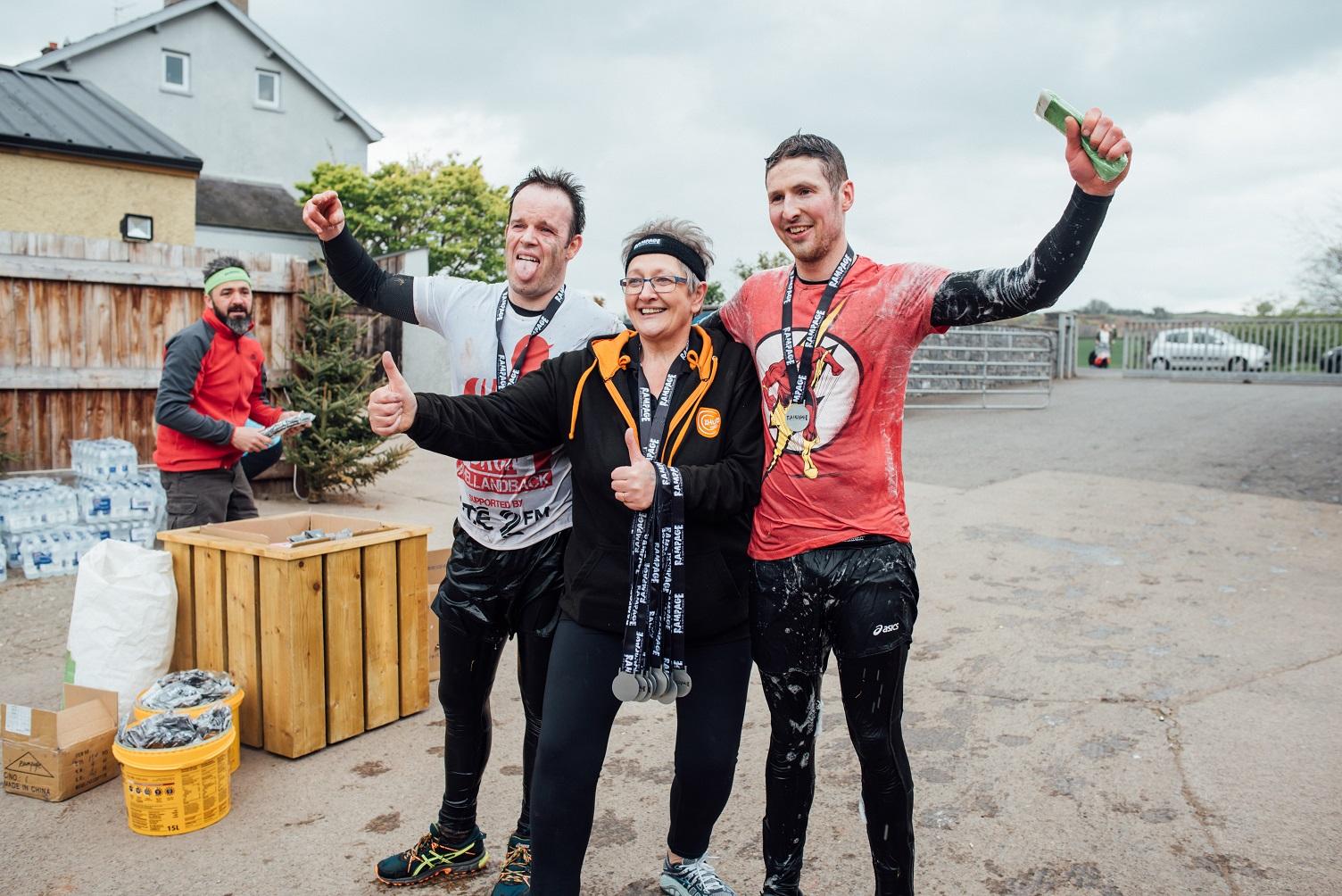 Carol Hub with 2 guys at finish line celebrating