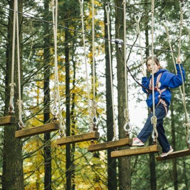 Kids TTA   girl in blue on wooden plank ropes